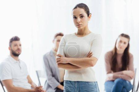 Photo pour Femme aux bras croisés en regardant la caméra pendant que les gens assis au cours de la session de thérapie de groupe - image libre de droit