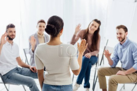 Photo for People sitting and raising hands during group therapy session - Royalty Free Image