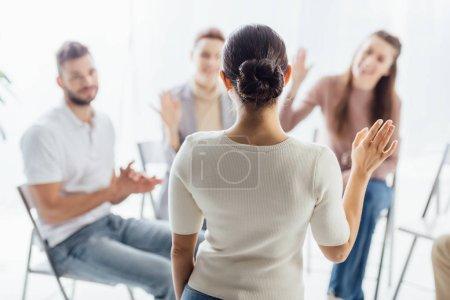 Photo pour Les gens assis et levant les mains au cours de la session de thérapie de groupe - image libre de droit