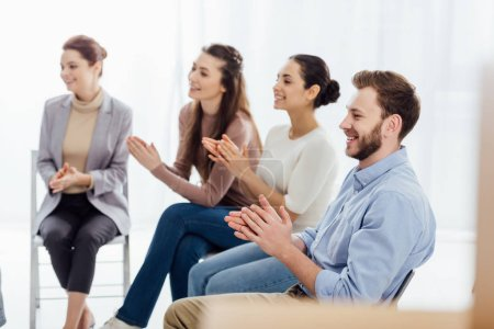 Foto de Grupo sonriente de personas sentadas y aplaudiendo durante la sesión de grupo de apoyo - Imagen libre de derechos
