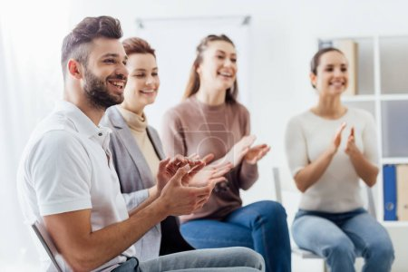 Photo for Smiling group of people sitting and applauding during support group session - Royalty Free Image