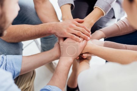 cropped view of people stacking hands during group therapy session