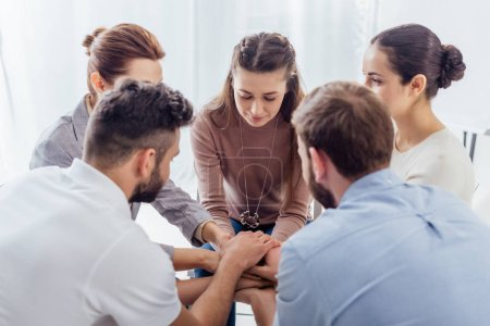 Photo for People sitting stacking hands during group therapy session - Royalty Free Image
