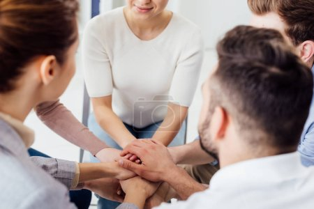 Photo for Partial view of people sitting and stacking hands during group therapy session - Royalty Free Image