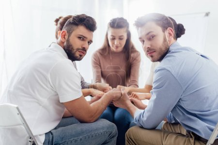 Photo for Selective focus of group of people sitting and stacking hands during therapy session - Royalty Free Image