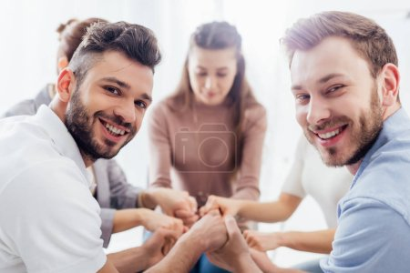 group of people sitting, smiling and stacking hands during therapy session