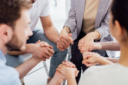 Photo for Cropped view of people holding hands during group therapy session - Royalty Free Image