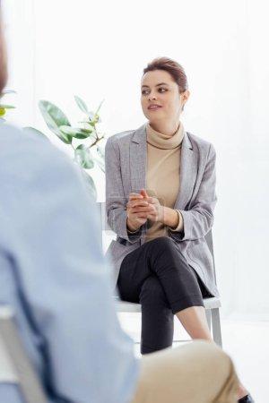 Photo pour Mise au point sélective de femme en vêtements assis et à la recherche de suite au cours de la séance de thérapie - image libre de droit