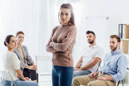 Foto de Mujer con los brazos cruzados mirando a cámara mientras personas sentadas en sillas durante la sesión de terapia de grupo - Imagen libre de derechos