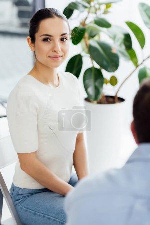 Photo pour Foyer sélectif de la femme assise et regardant la caméra pendant la séance de thérapie - image libre de droit