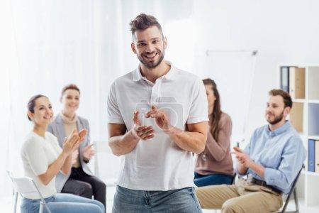 Photo pour Homme regardant la caméra et applaudi pendant que les gens assis au cours de la session de thérapie de groupe - image libre de droit