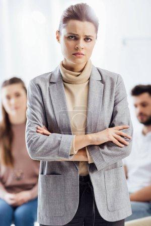 Photo pour Femme triste en tenues en regardant la caméra au cours de la session de thérapie de groupe - image libre de droit