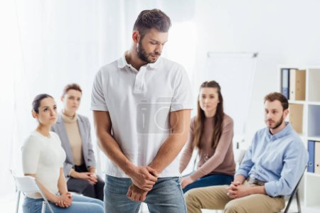 Photo pour Foyer sélectif de l'homme regardant loin tandis que les gens assis pendant la séance de thérapie de groupe - image libre de droit
