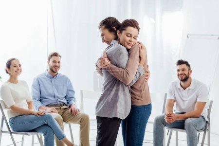 Foto de Mujeres abrazando mientras que grupo de gente sentada y sonriente durante la sesión de terapia - Imagen libre de derechos