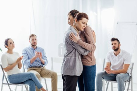 women hugging while group of people sitting and applauding during therapy session