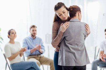 Photo pour Mise au point sélective des femmes étreindre au cours de la session de thérapie de groupe - image libre de droit