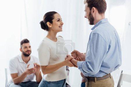 Foto de Bella mujer sonriente cogidos de la mano con el hombre durante la sesión de terapia de grupo - Imagen libre de derechos