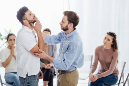 Photo pour Homme de consoler un autre homme pendant que les gens assis sur des chaises au cours de la session de thérapie de groupe - image libre de droit