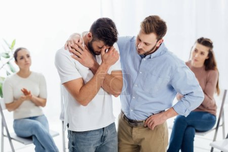 man cheering another man while people sitting on chairs during group therapy session