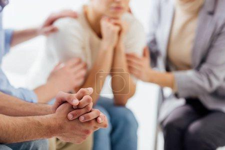 Photo pour Vue recadrée de l'homme avec les mains pliées pendant la séance de thérapie de groupe - image libre de droit