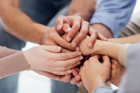 Photo for Cropped view of people stacking hands during group therapy session - Royalty Free Image