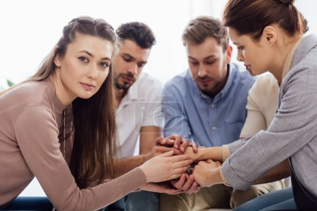 Photo for Group of people sitting and stacking hands during therapy session - Royalty Free Image