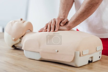 Photo for Partial view of man using chest compression technique on dummy during cpr training - Royalty Free Image