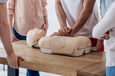 Photo pour Vue recadrée de l'homme effectuant une compression thoracique sur mannequin pendant la classe d'entraînement cpr - image libre de droit