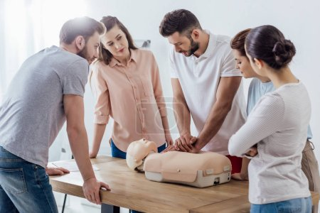 Photo for Group of people looking at man performing cpr on dummy during first aid training - Royalty Free Image