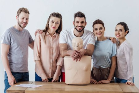 Photo for Group of people with cpr dummy looking at camera and smiling during first aid training class - Royalty Free Image