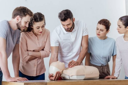 Photo for Group of concentrated people with cpr dummy during first aid training class - Royalty Free Image