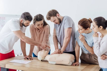 Photo for Group of people with instructor performing cpr on dummy during first aid training - Royalty Free Image