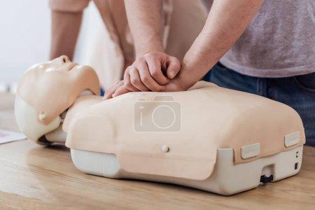 Photo pour Vue partielle de l'homme effectuant la compression thoracique sur mannequin pendant la classe d'entraînement cpr - image libre de droit