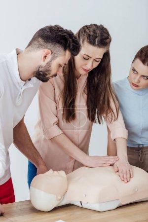 Photo pour Belle femme effectuant la compression thoracique sur mannequin pendant le cours de formation cpr - image libre de droit