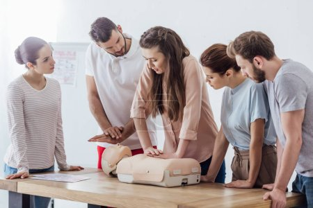 Photo for Group of concentrated people performing cpr on dummy during first aid training - Royalty Free Image