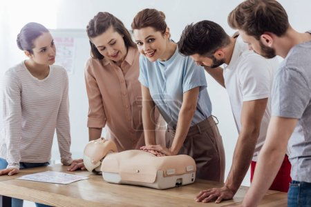 Photo for Beautiful smiling woman looking at camera while performing cpr on dummy during first aid training with group of people - Royalty Free Image