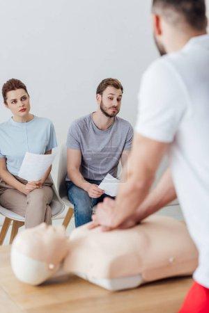 Photo pour Vue arrière de l'instructeur effectuant la compression thoracique sur mannequin pendant la classe d'entraînement cpr avec un groupe de personnes - image libre de droit