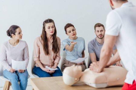 Photo pour Vue arrière de l'instructeur effectuant cpr sur mannequin pendant la formation de premiers soins avec un groupe de personnes - image libre de droit