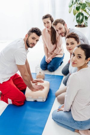 Photo for Group of people with instructor looking at camera during first aid training - Royalty Free Image