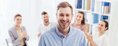 Photo pour Prise de vue panoramique de l'homme souriant en regardant la caméra pendant que les gens assis au cours de la session de thérapie de groupe - image libre de droit