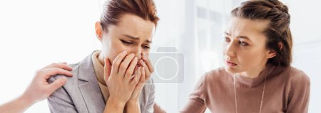 Photo for Panoramic shot of woman consoling another crying woman during therapy meeting - Royalty Free Image