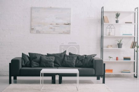 Photo for Black sofa near coffee table and rack in modern living room - Royalty Free Image
