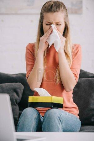 Blondine niest in Gewebe, während sie zu Hause auf dem Sofa sitzt