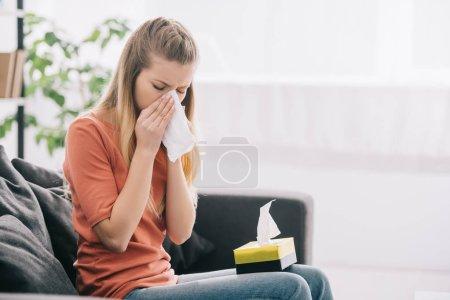 Foto de Atractiva mujer rubia estornudando mientras está sentada en el sofá con caja de pañuelos - Imagen libre de derechos
