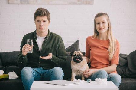 Photo pour Bel homme allergique au chien tenant un verre d'eau et des pilules près de femme gaie avec carlin mignon - image libre de droit