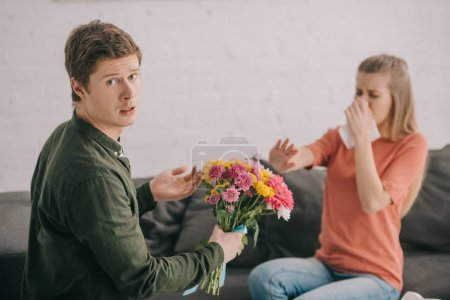 Photo for Upset man holding flowers and looking at camera near blonde woman with pollen allergy sneezing in tissue - Royalty Free Image