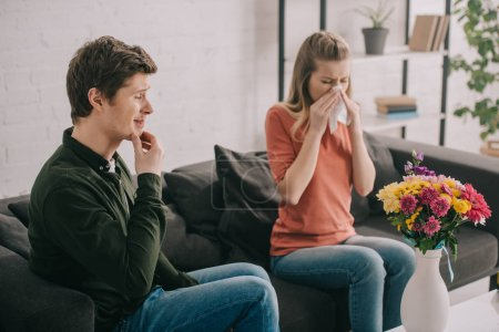 Photo for Pensive man looking at vase with flowers near sneezing blonde girl with pollen allergy - Royalty Free Image