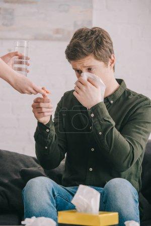 Photo pour Vue recadrée de la femme tenant un verre d'eau et des pilules près de l'homme éternuant dans les tissus - image libre de droit