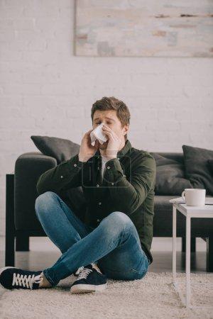 Mann sitzt mit gekreuzten Beinen auf Teppich und niest in Taschentuch neben Couchtisch mit Tasse Kaffee