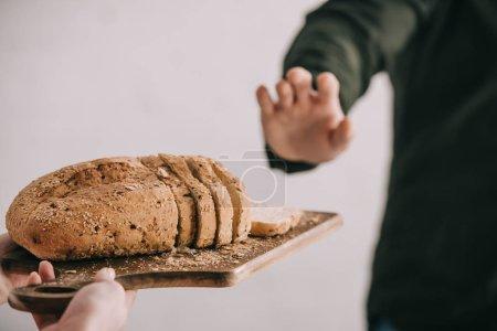 Photo pour Vue recadrée de femme tenant la planche à découper avec du pain tranché près de l'homme avec l'intolérance au gluten, isolé sur fond gris - image libre de droit